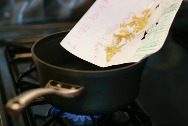 Macaroni being slid off of a macaroni art drawing into a pot of water over a lit burner