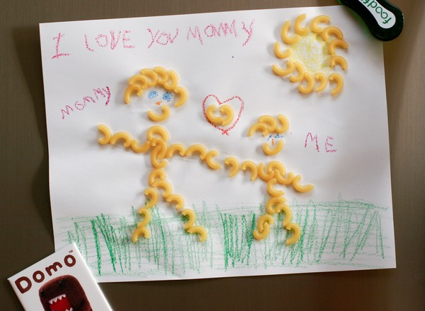 A childish macaroni art drawing of an adult and a child standing on grass with the sun overhead and a heart between them; labeled, 'I love you mommy'