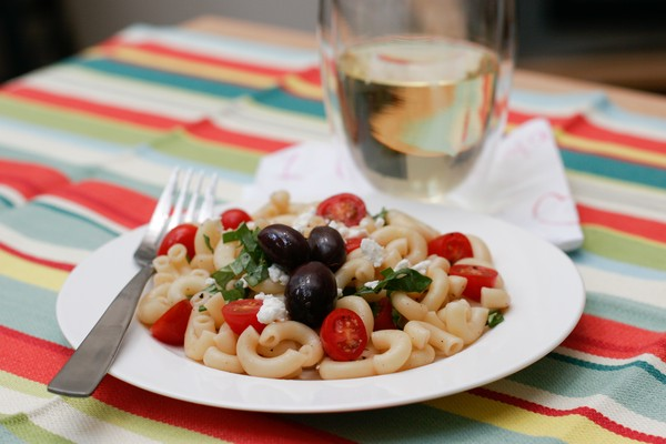 Finished macaroni salad with olives tomatoes and feta crumbles on a white plate with a metal fork; a glass of white wine is behind the plate on a napkin; all sit on a colorful tablecloth