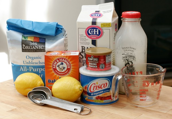 A bag of flour, a box of ultrafine sugar, a jar of milk, two lemons, a box of baking soda, a tin of baking powder, a can of Crisco, a measuring cup, and measuring spoons