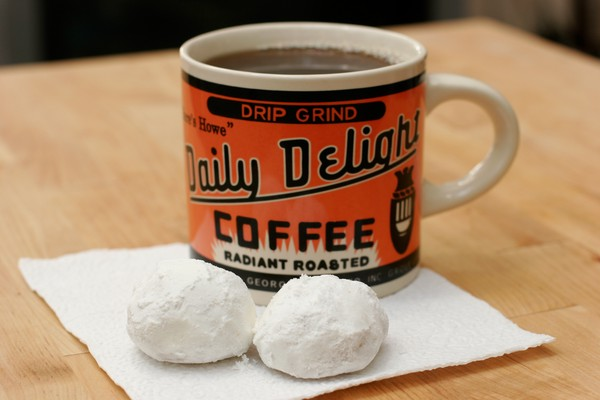 Two biscuits and a cup of black coffee on a white napkin; the coffee mug says, 'drip grind, Daily Delight Coffee, radiant roasted' in black lettering on a bright orange background